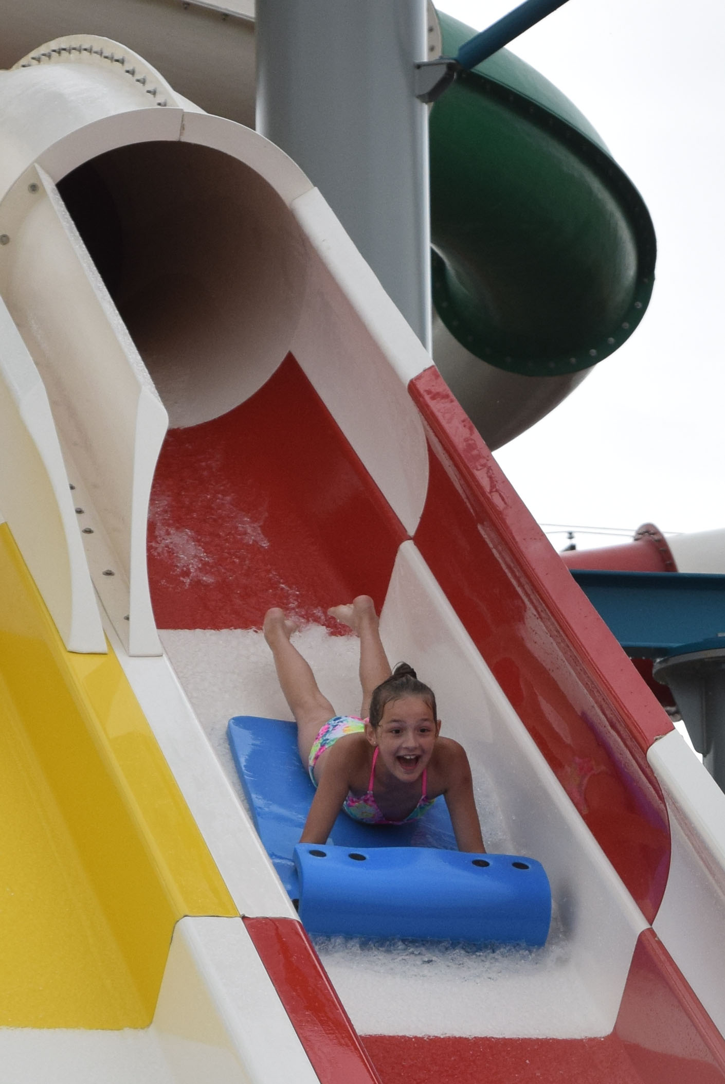 Smiling girl on red slide cropped