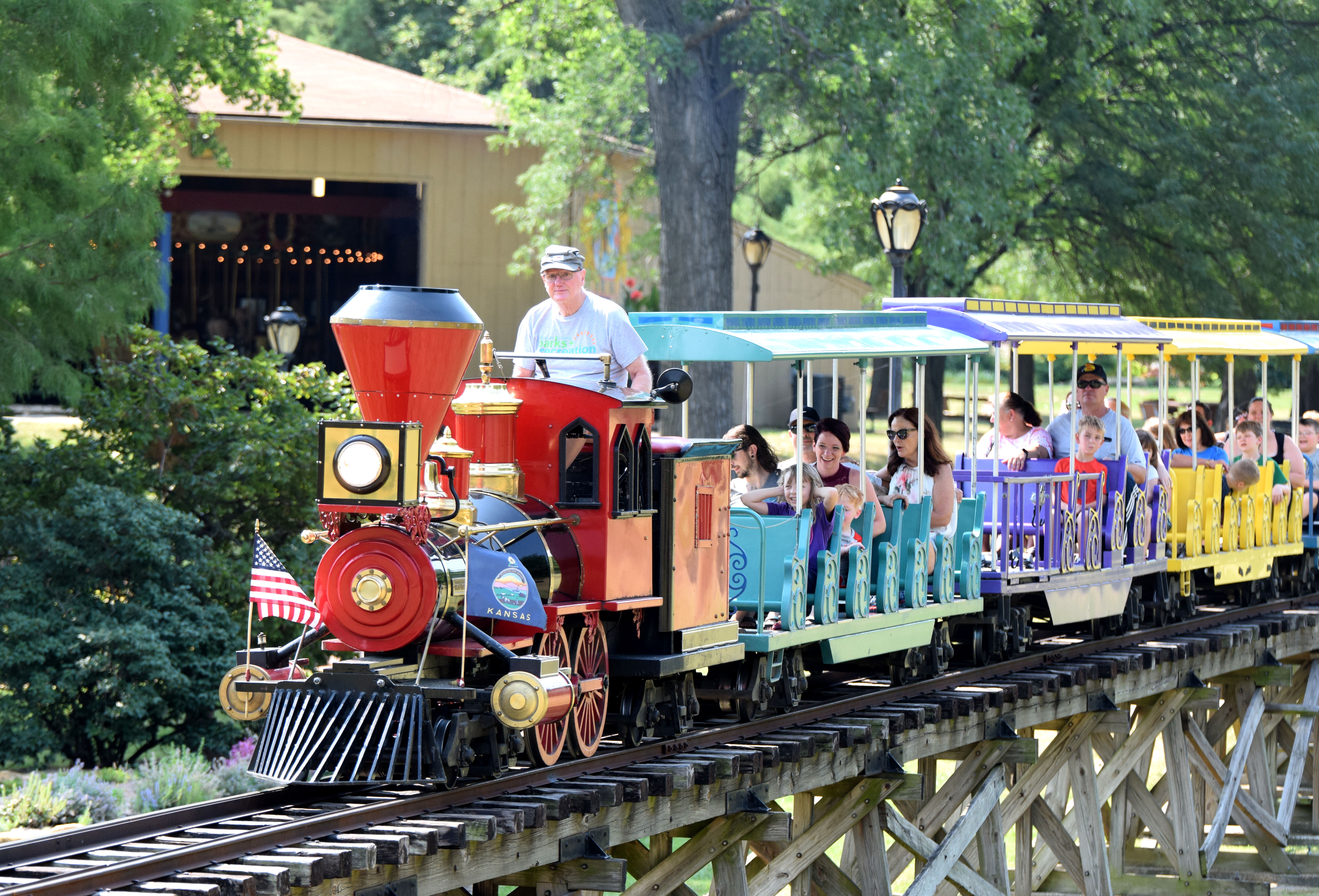 Mini-train on trestle in front of carousel