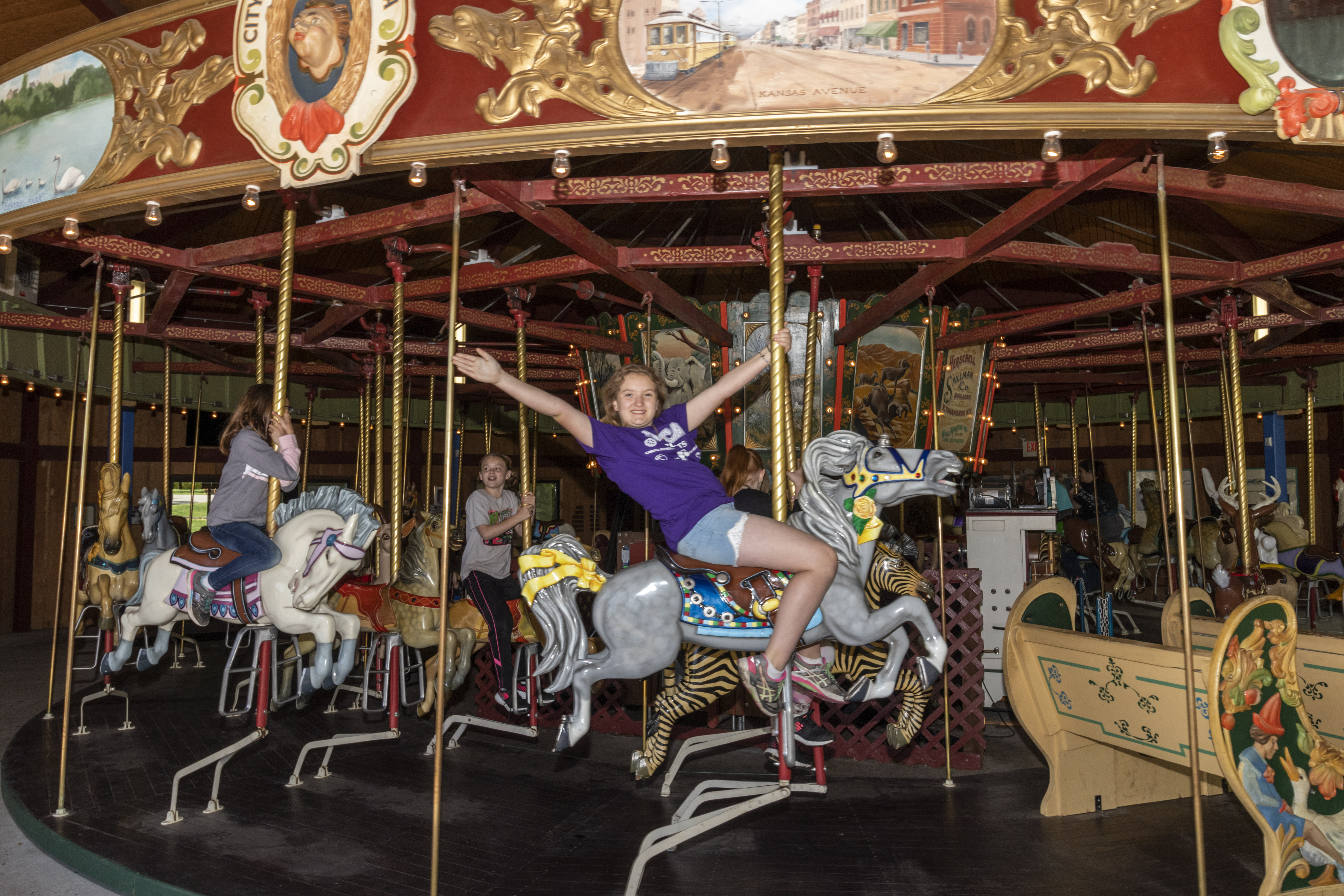Little girl with outstretched hands riding carousel